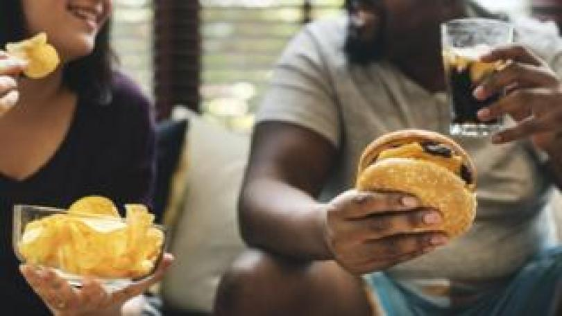 A woman and a man eat crisps and a burger on a sofa