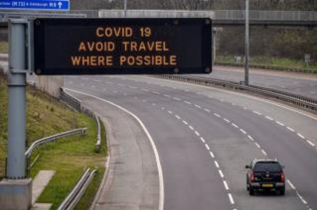 A sign on the M8 motorway advises motorists to avoid travel where possible