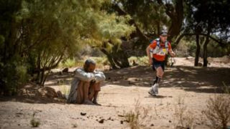 A competitor runs past an inhabitant during the stage 3 of the 34th edition of the Marathon des Sables between Kourci Dial Zaid and Jebel El Mraïer in the southern Moroccan Sahara desert, Tuesday 9 April 2019