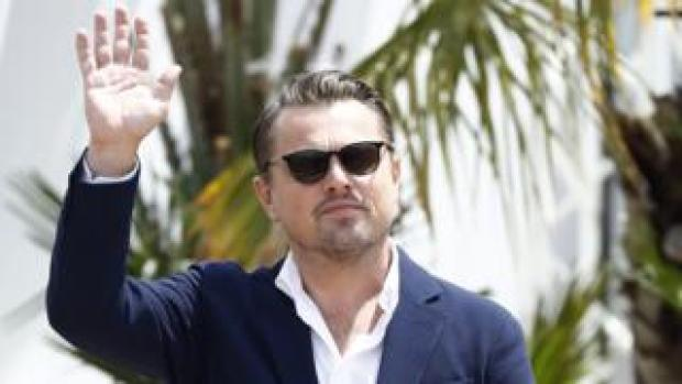 Leonardo DiCaprio waving, behind him is a tree