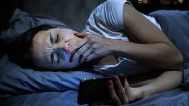 A woman yawns as she checks her smartphone while in bed