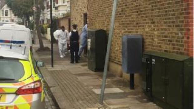 Forensic officers and police at the scene in Southfields