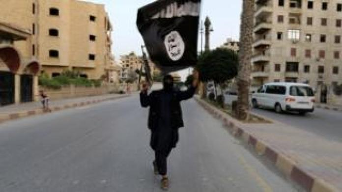 An IS militant waves a flag in Raqqa, Syria, in 2014