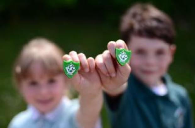 A girl and a boy hold up a green Blue Peter badge