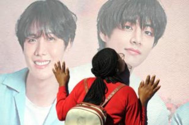 Fan kisses poster of BTS