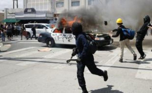 An LAPD vehicle burns after being set alight by protestors during demonstrations following the death of George Floyd, in Los Angeles, California, 30 May 2020