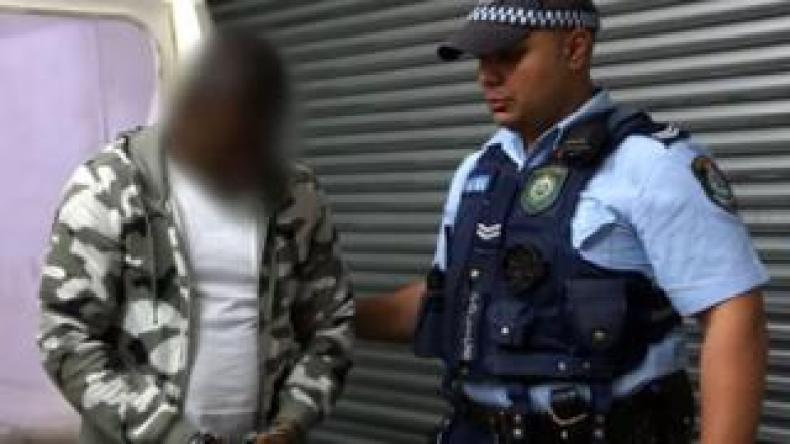 The alleged ringleader, shown in an image blurred by New South Wales Police, is accompanied by a police officer