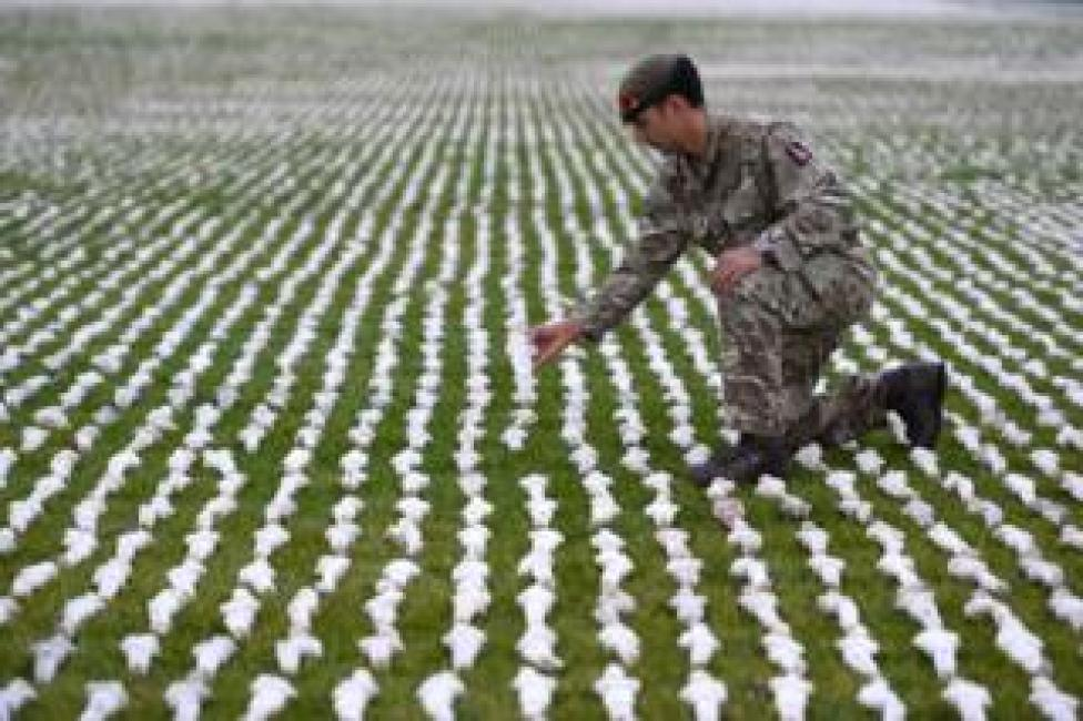 Captain James Pugh places a figure among artist Rob Heard's installation Shrouds of the Somme