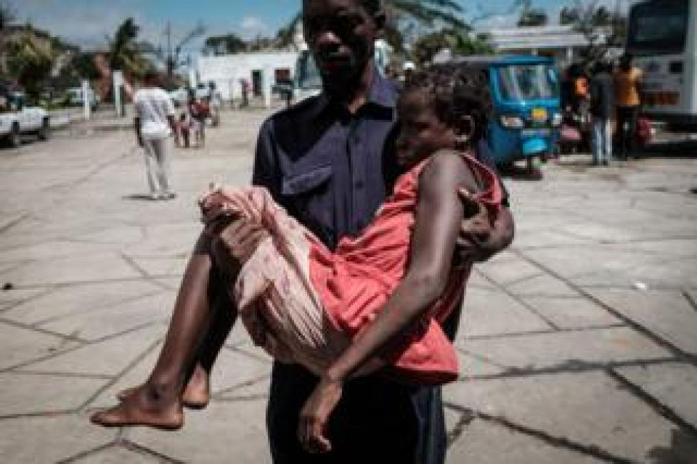 A girl who was evacuated by boat from the isolated district of Buzi is carried by a Red Cross staff on her arrival at Samora M. Machel secondary school turned evacuation center in Beira, Mozambique, on March 21, 2019.