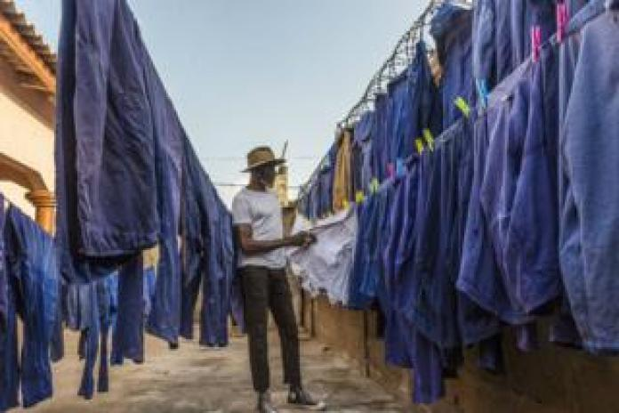 Amah Ayivi inspects rows of blue worker jackets.