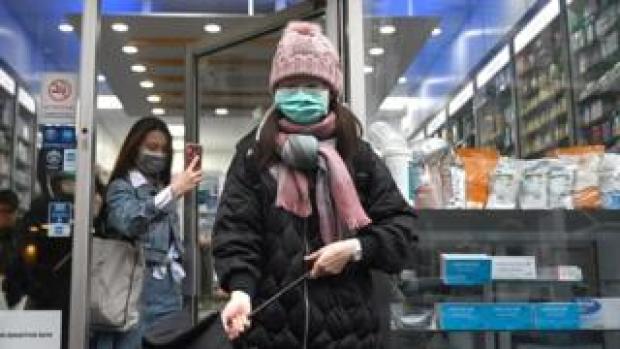 Women wear masks as they shop in London