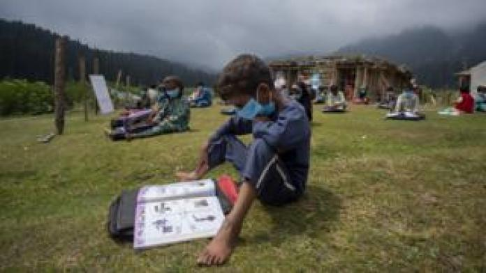 A boy reads a book during an outdoor class.