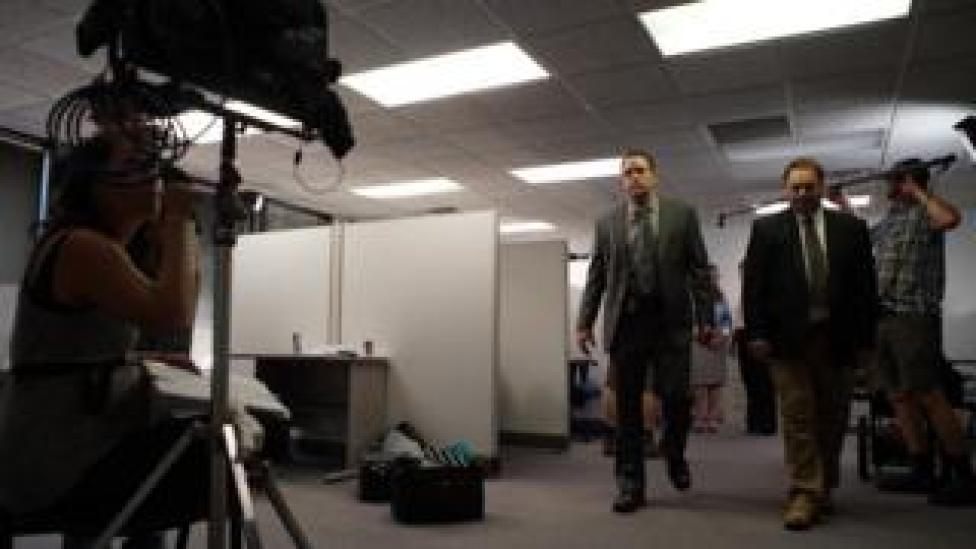 Behind-the-scenes shots shows actors as detectives being filmed by crewmembers