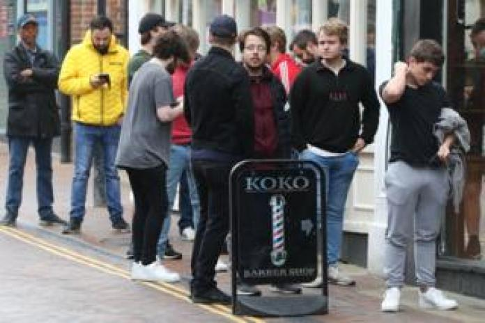Men line up on the street to enter a hair salon