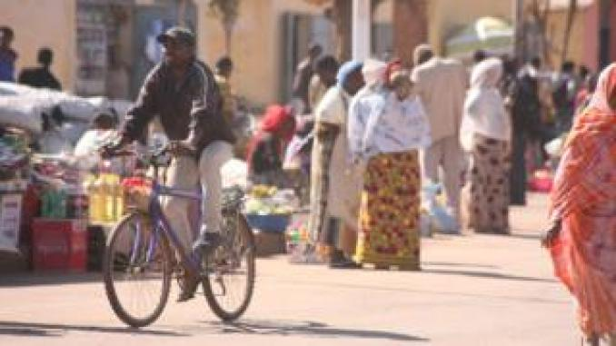 A man on a bicycle riding past a street market in Asmara, Eritrea