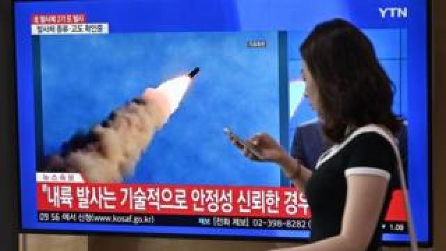 A woman walks past a television news screen showing file footage of a North Korean missile launch, at a railway station in Seoul on September 10, 2019.