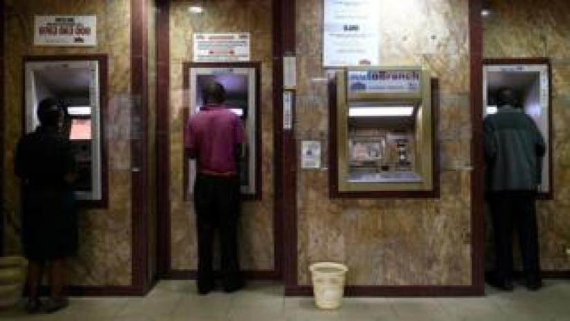 Kenyans withdrawing cash from an ATM