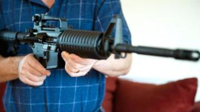 File picture of a man holding a Colt AR-15 semi-automatic rifle