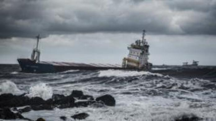 Ship heading for harbour in rough seas