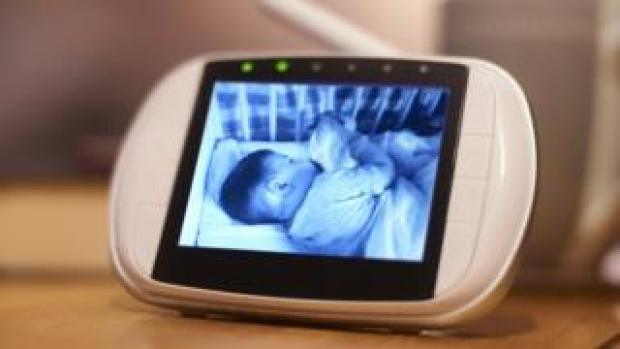 A black and white video image of a baby sleeping is seen on a baby monitor