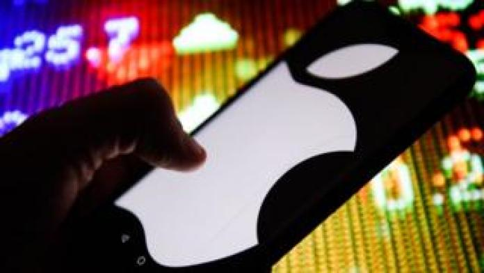 The Apple logo can be seen on a mobile phone.