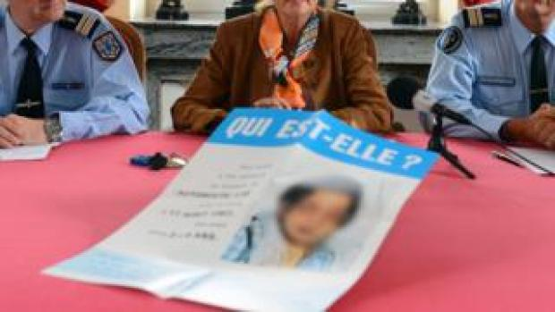 """Police and a prosecutor present a leaflet to the media with a picture of the girl and a message reading """"Who is she?"""""""