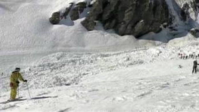 A screenshot of a video shows a large snowdrift and affected skiers