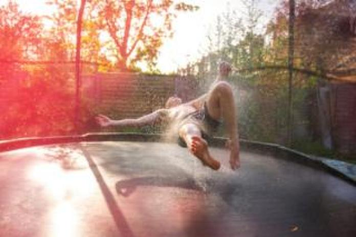A person bouncing on a trampoline in a garden