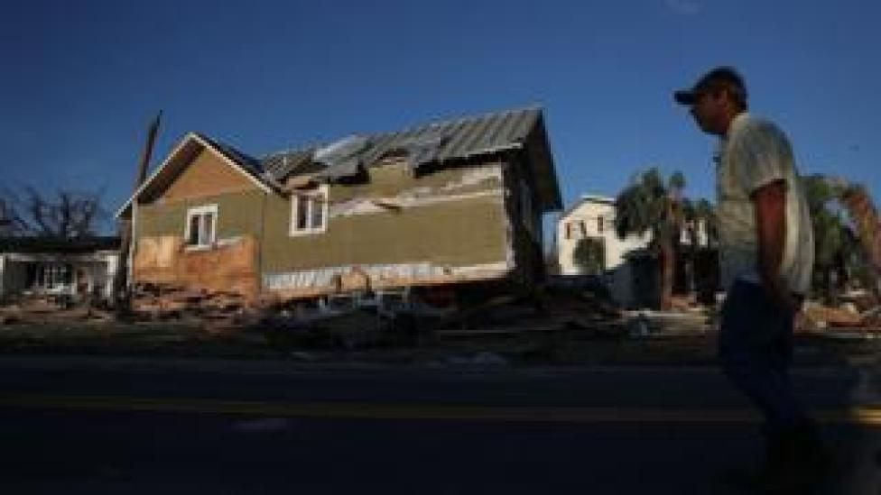 NEWS A man in Mexico Beach, Florida walks past a home that was knocked from its foundation