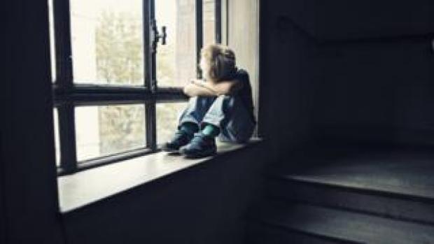 Boy sat by a window