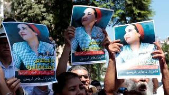 Moroccan activists hold posters of Hajar Raissouni at a protest outside the Rabat tribunal