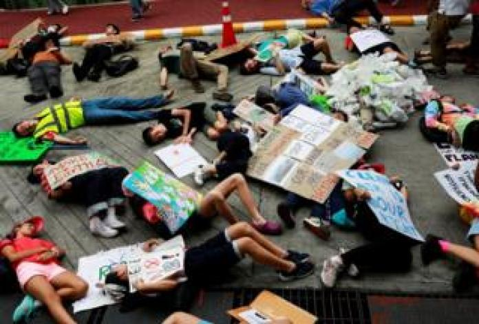 Activists play dead on the floor with banners