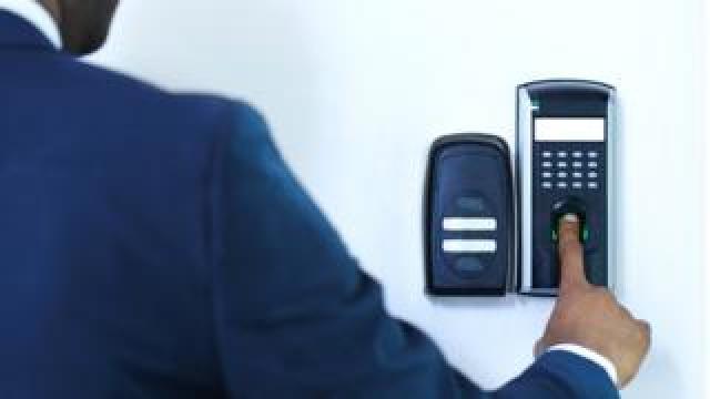 A man using a fingerprint scanner on a wall