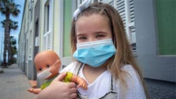 فتاة صغيرة تحمل دمية