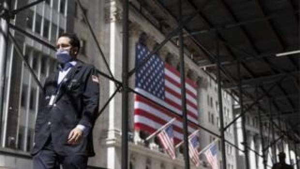 A trader walks past the New York Stock Exchange in New York, New York, USA, on 03 September 2020. The Dow Jones industrial average was down nearly 900 points today