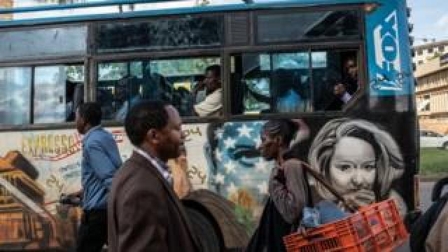 A privately owned minibus with a mural of the American television drama, 24, passes a bus stop in Nairobi, Kenya - Tuesday 4 December 2018