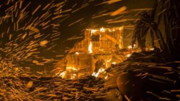 Strong winds blow embers from burning houses during the Woolsey Fire on November 9, 2018
