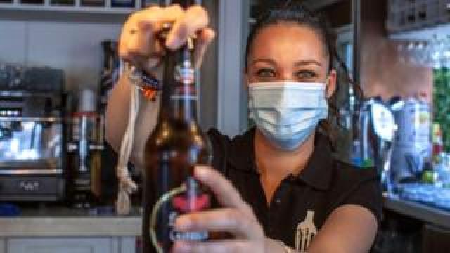 A waitress in a socially-distanced bar in Spain