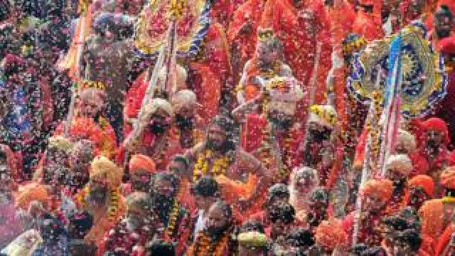 Indian devotees shower flower petals on Hindu holy men during a religious procession towards the Sangam area during the 'royal entry' for the upcoming Kumbh Mela festival in Allahabad on January 2, 2019