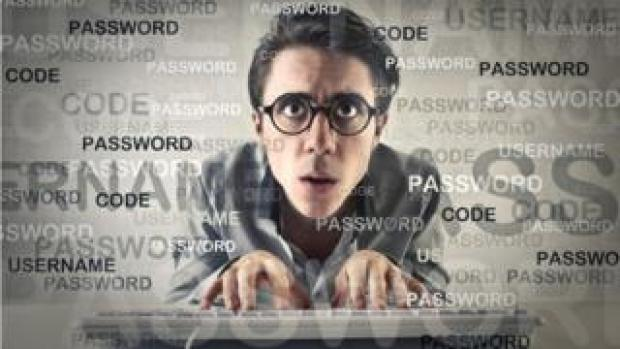 Geeky man typing on keyboard surrounded by password graphics