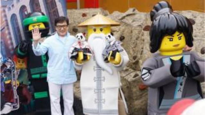 Jackie Chan poses with Ninjago Lego figures
