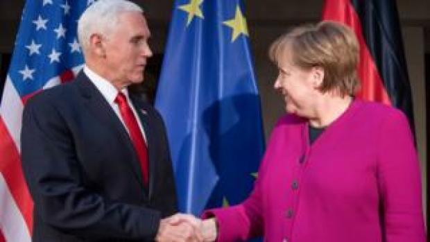 German Chancellor Angela Merkel (R) and US Vice President Mike Pence shake hands at a photo call during the 55th Munich Security Conference