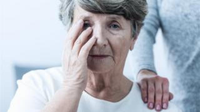 Older woman touching her face
