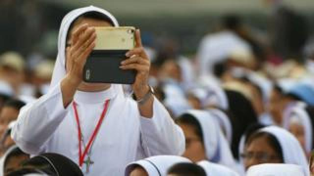 A nun takes a photo with an iPhone