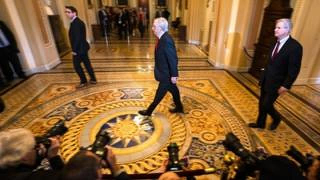 Senate Majority Leader Mitch McConnell (C) walks to the Senate floor at the start of the trial
