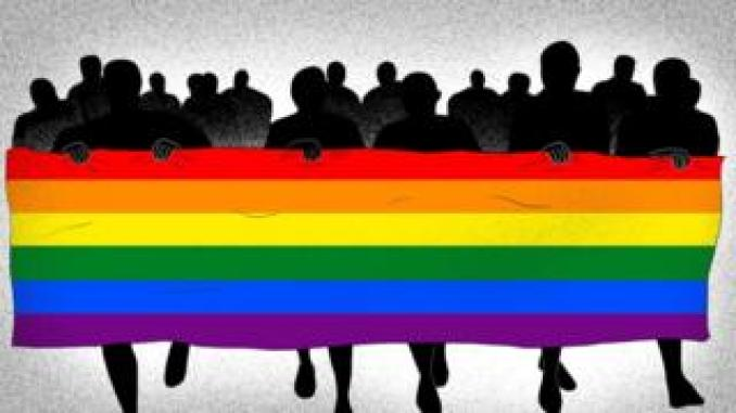 Parade of shadowed people holding a rainbow flag