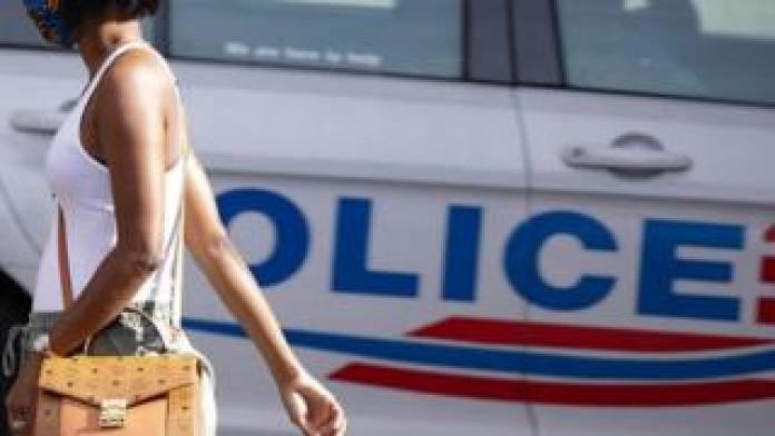 Black woman walks past a police car in Washington DC. May 2020