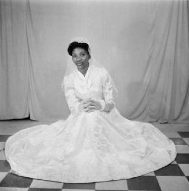 A woman poses on the studio floor in a white wedding gown, lace gloves and veil.