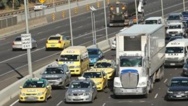 Taxi drivers drive slowly along Melbourne's Tullamarine Freeway