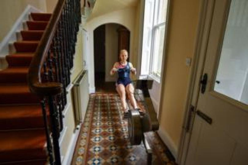 An athlete using a rowing machine in a hallway